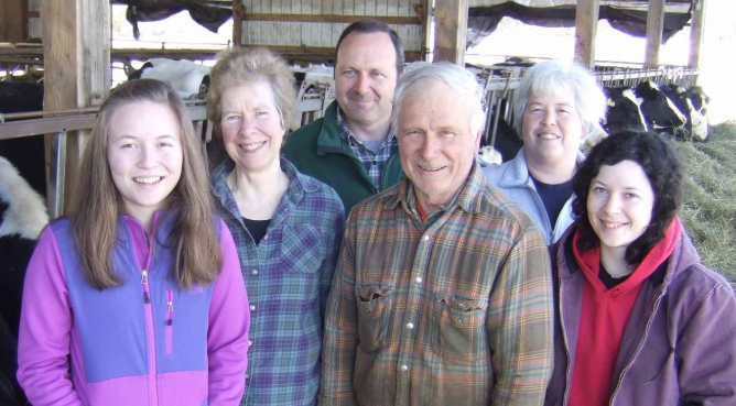 Family members on a farm with cows in background