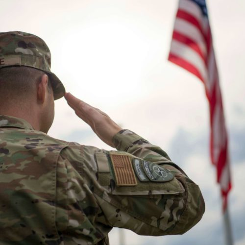 soldier in camouflage saluting American flag